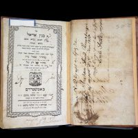 open book, showing title page on left and blank flyleaf on the right. The page on the right has large, cursive handwriting in brown ink reading Abraham David Rosenberger.